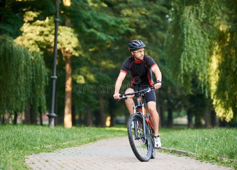男性骑自行车者训练在绿色公园 免版税图库摄影