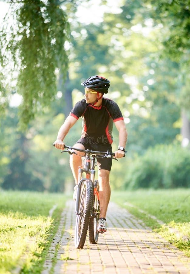 男性骑自行车者训练在绿色公园 免版税库存照片