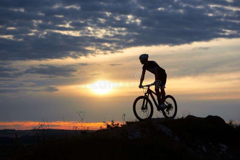 男性骑自行车者骑马自行车剪影在岩石的在山 免版税库存照片