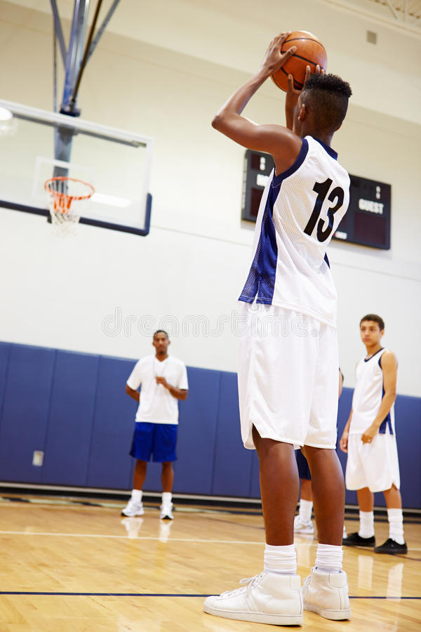男性高中蓝球运动员射击惩罚 免版税库存图片