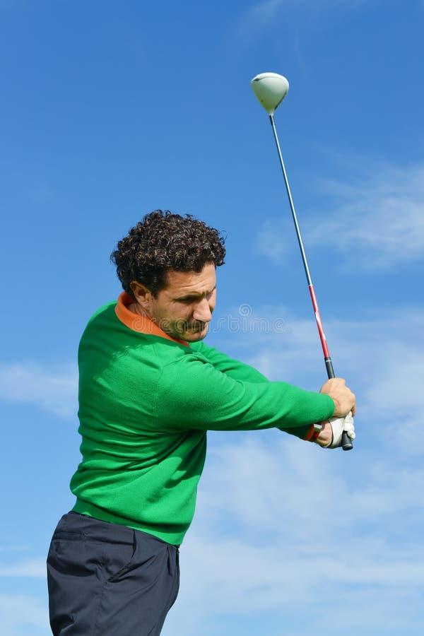 男性高尔夫球摇摆在一美好的天 库存照片