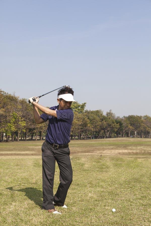 男性高尔夫球运动员摇摆的高尔夫球 免版税库存图片