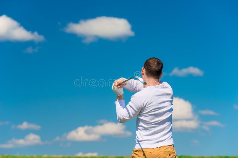 男性高尔夫球运动员,当击中从后面时的球视图 免版税库存照片