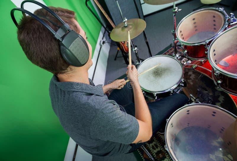 男性鼓手佩带的耳机,当执行时 免版税库存照片