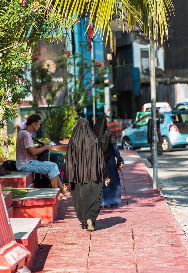 男性,马尔代夫- 2016年11月, 27日:一黑burqa的妇女在城市街道上 复制文本的空间 垂直 库存图片