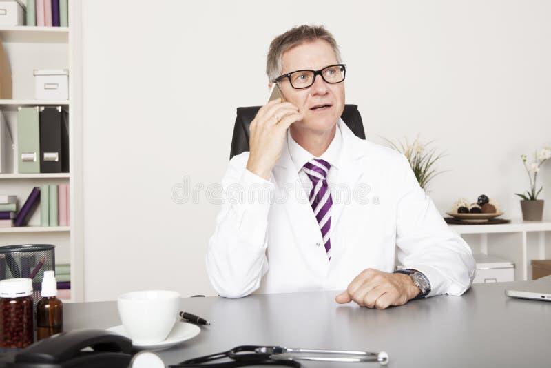 男性医师叫客户通过电话 免版税库存照片
