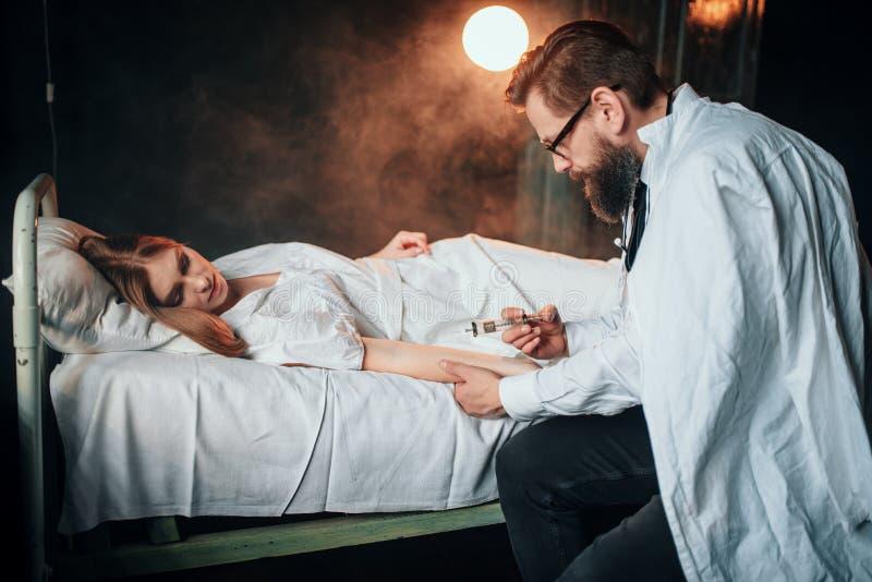 男性医生做注射器射入给病的妇女 免版税库存图片