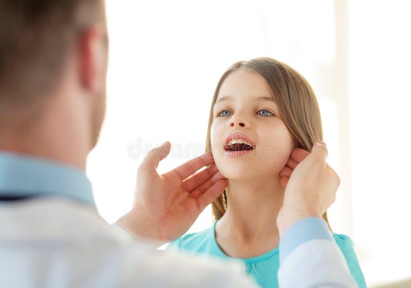 男性医生检查小女孩淋巴结 免版税库存图片
