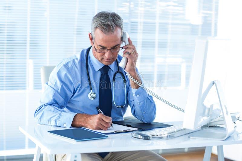 男性医生谈话在电话在医院 免版税图库摄影