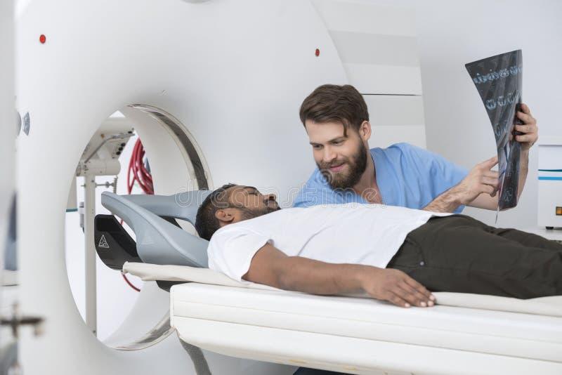 男性医生Showing X-ray To说谎在CT扫描器的Patient 免版税库存图片