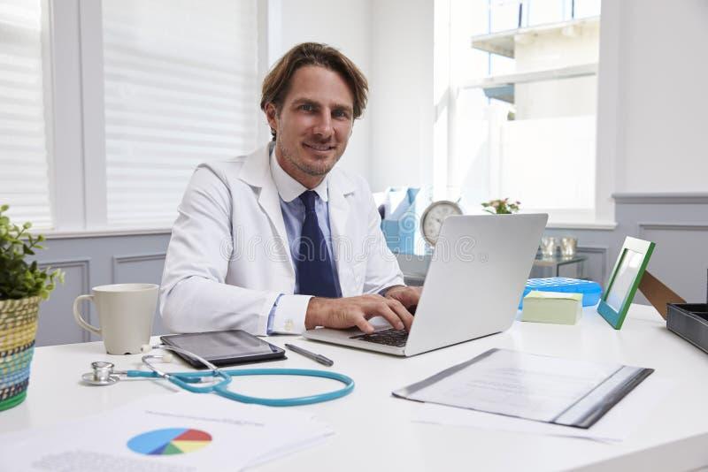 男性医生Sitting At在膝上型计算机的Desk Working在办公室 图库摄影