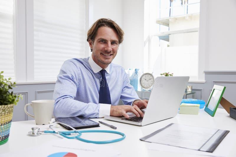 男性医生Sitting At在膝上型计算机的Desk Working在办公室 库存照片