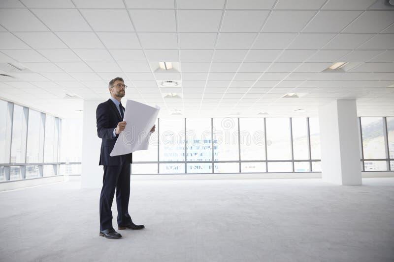男性建筑师在看计划的现代空的办公室 免版税图库摄影