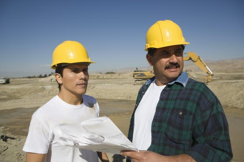 男性建筑师谈论在建造场所 免版税库存照片