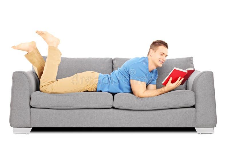 年轻男性说谎在沙发和读书 库存图片