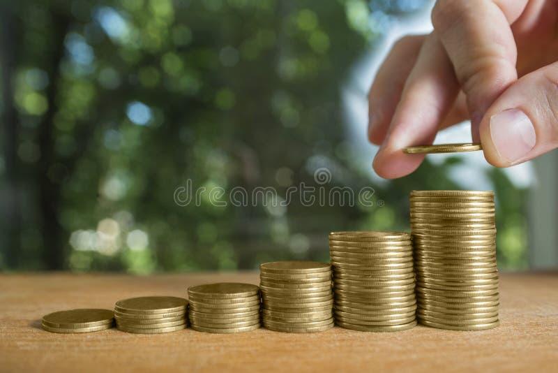 男性` s手在金钱楼梯上把硬币堆放 企业增长的和保存的金钱概念 库存图片