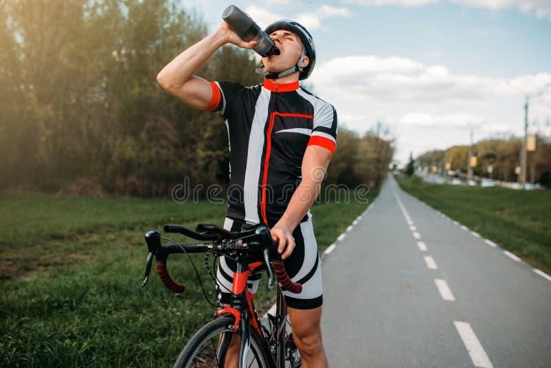 男性bycyclist喝水,当训练时 免版税库存照片