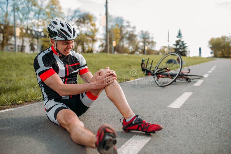 男性bycyclist跌下自行车并且击中了他的膝盖 库存照片