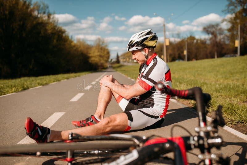 男性bycyclist跌下自行车并且击中了他的膝盖 免版税图库摄影