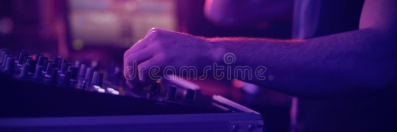男性dj混合的音乐的中间部分在酒吧的 免版税库存图片