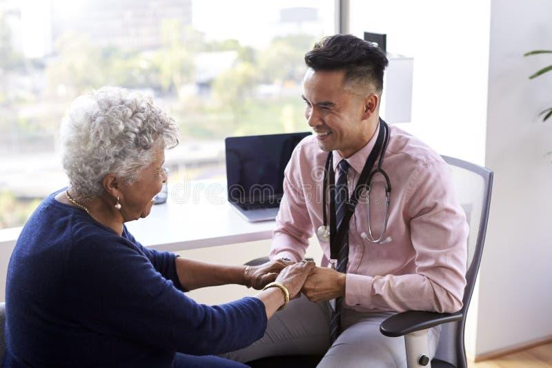 男性In Office Reassuring Senior医生女性患者和握她的手 免版税库存照片