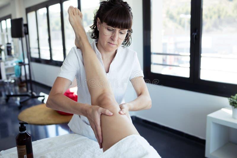 男按摩师在温泉中心的按摩孕妇的腿 库存图片