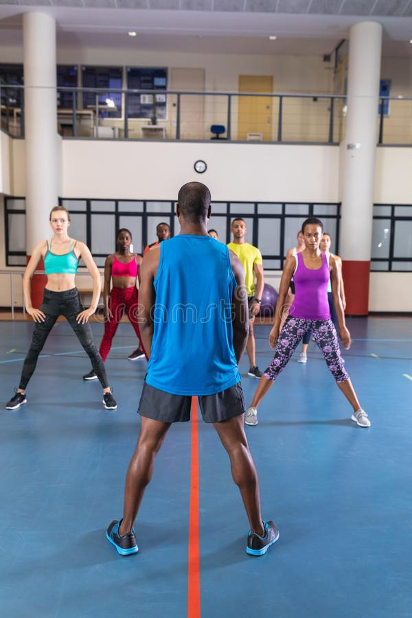 男教练员在健身中心训练练瑜伽 免版税库存图片