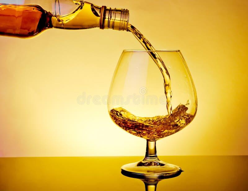 男服务员倾吐的一口威士忌酒在典雅的典型的科涅克白兰地玻璃的白兰地酒在桌上 免版税库存照片
