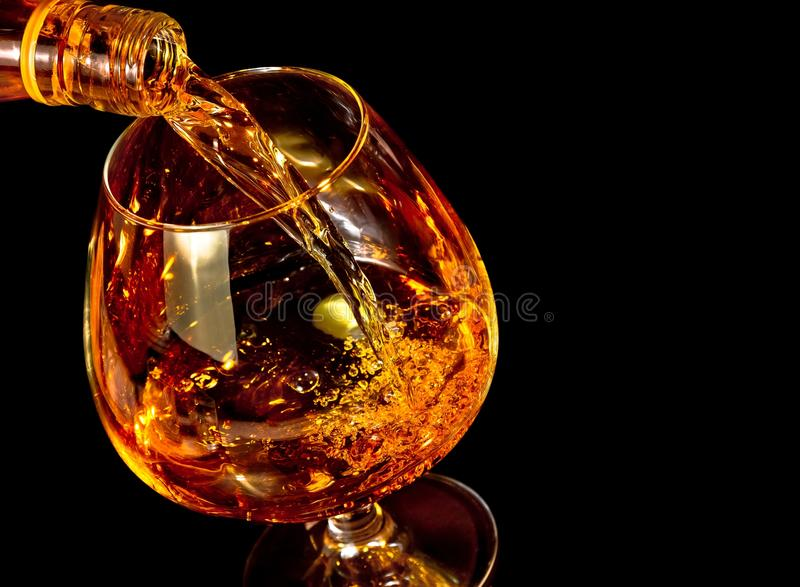 男服务员倾吐的一口威士忌酒在典雅的典型的科涅克白兰地玻璃的白兰地酒在黑背景 免版税库存图片
