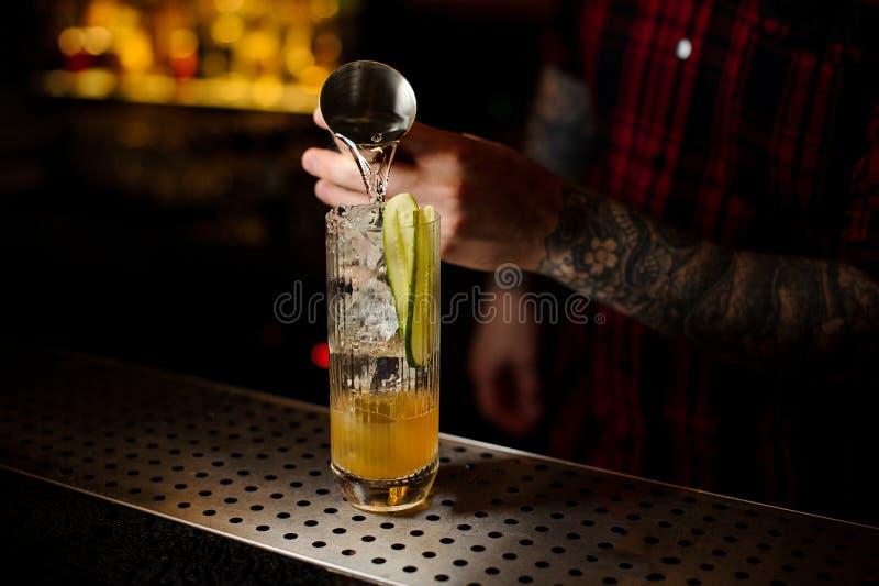 男服务员倾吐的杜松子酒到一块玻璃里用做新cockt的黄瓜 免版税库存照片