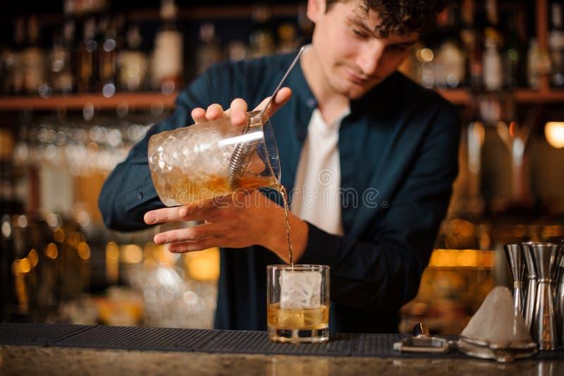 男服务员准备一个古板的酒精鸡尾酒,加威士忌酒到冰 库存图片