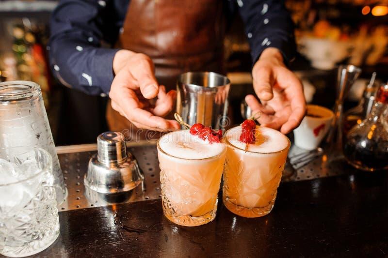 男服务员准备了两个琥珀色的颜色的酒精鸡尾酒酸混合用樱桃和冰 免版税图库摄影