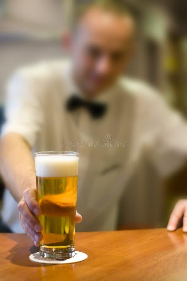 男服务员啤酒服务 免版税库存图片