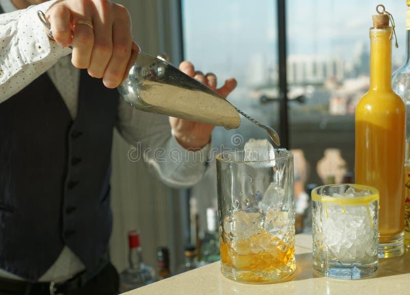 男服务员增加冰到鸡尾酒 免版税库存照片
