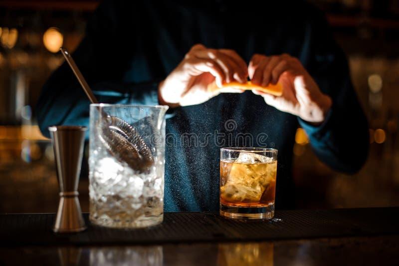 男服务员完成准备古板一个酒精的鸡尾酒加苦涩的桔子 免版税库存照片