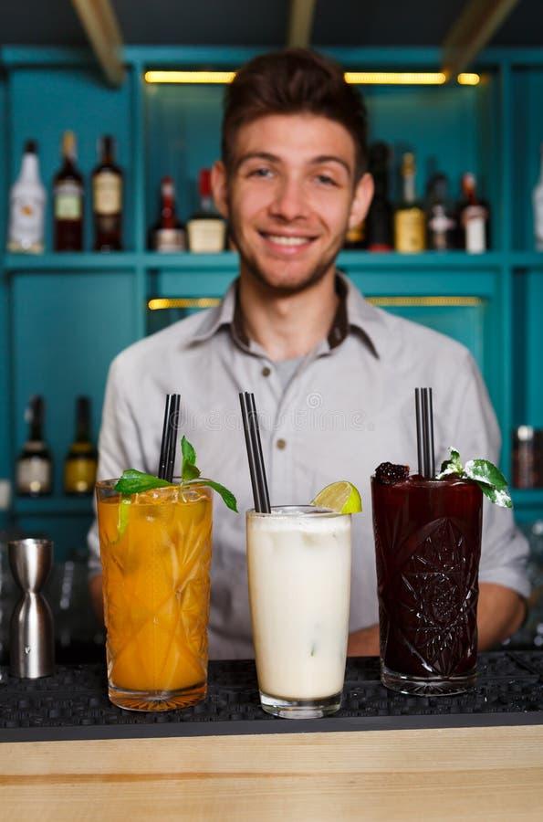 年轻男服务员提供在夜总会酒吧的酒精鸡尾酒 库存照片