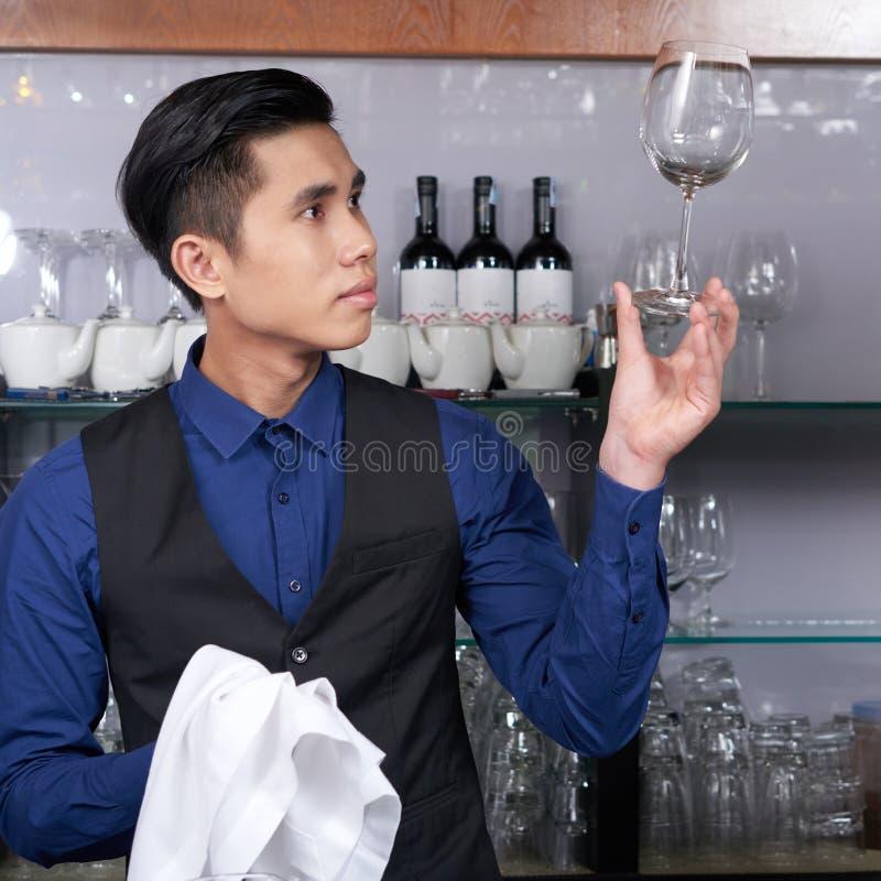 男服务员清洗的玻璃 免版税库存照片