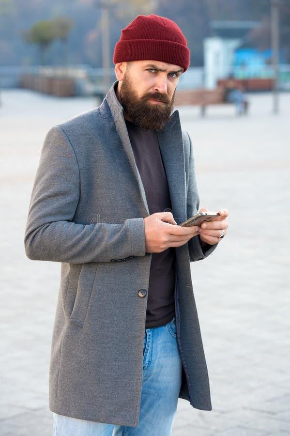 男服和男性时尚概念 人有胡子的行家时髦的时兴的外套和帽子 时髦的现代成套装备帽子 免版税库存图片
