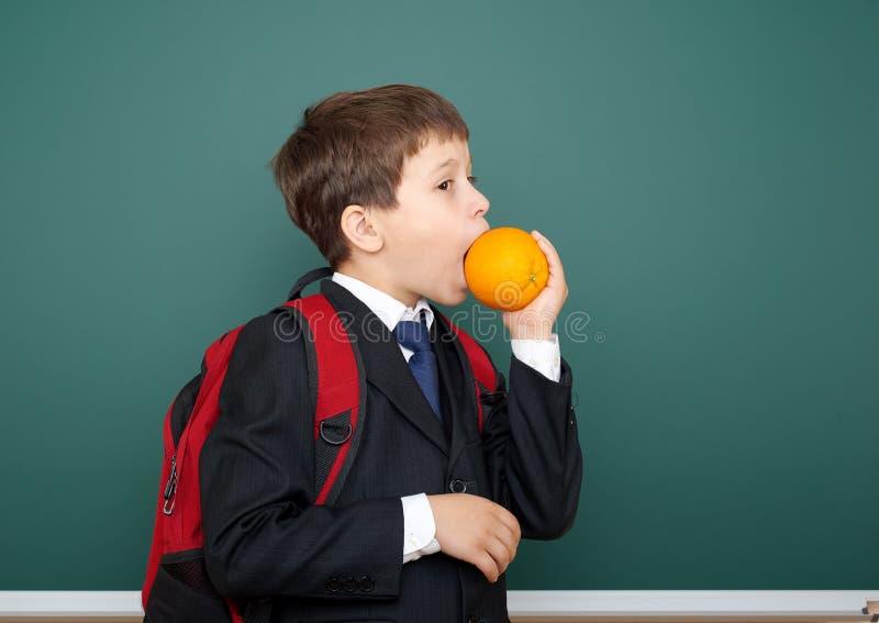 男生吃在黑衣服的桔子在与红色背包的绿色黑板背景,教育概念 免版税库存照片