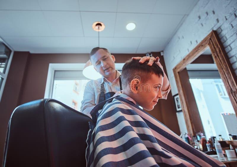 男生在现代理发店enjoing理发的过程从expirienced理发师的 库存照片