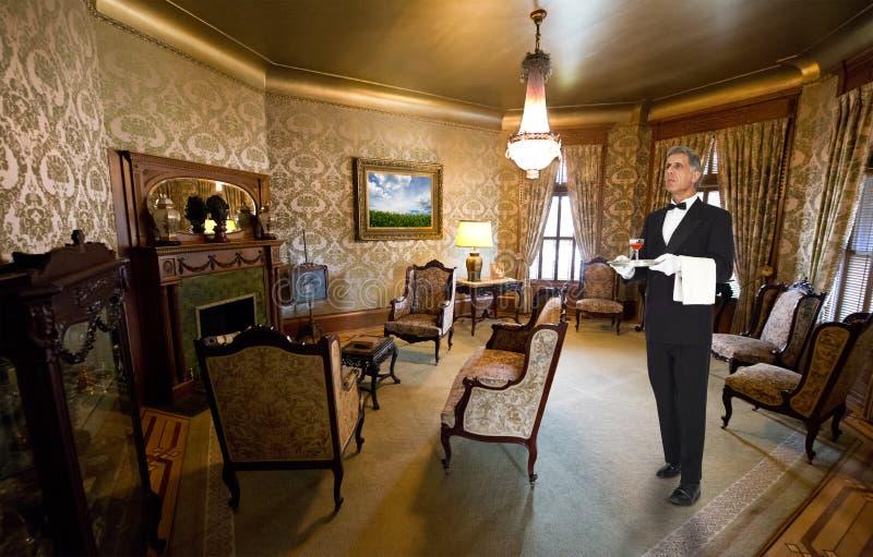 男管家或侍者职员在维多利亚女王时代的豪宅客厅里 库存图片