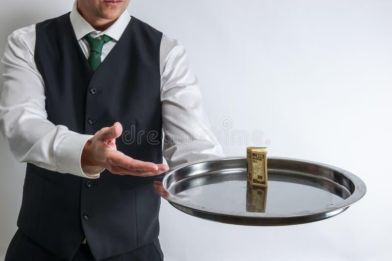 男管家/侍者拿着有十美金的一个银色盘子 免版税库存照片