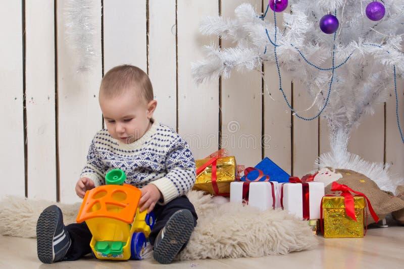 男婴在圣诞节杉树下 免版税图库摄影