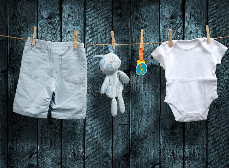 男婴衣裳和被充塞的兔宝宝在晒衣绳 免版税库存图片