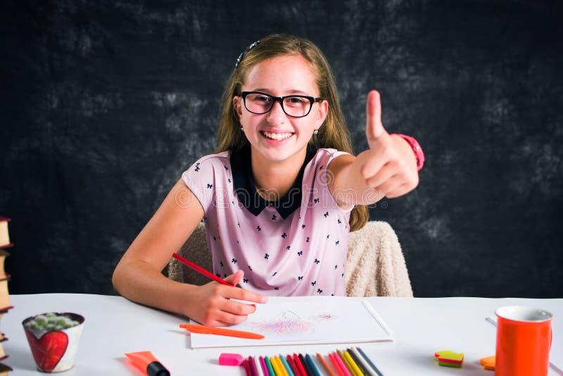 与五颜六色的铅笔的愉快的女孩图画 免版税库存照片