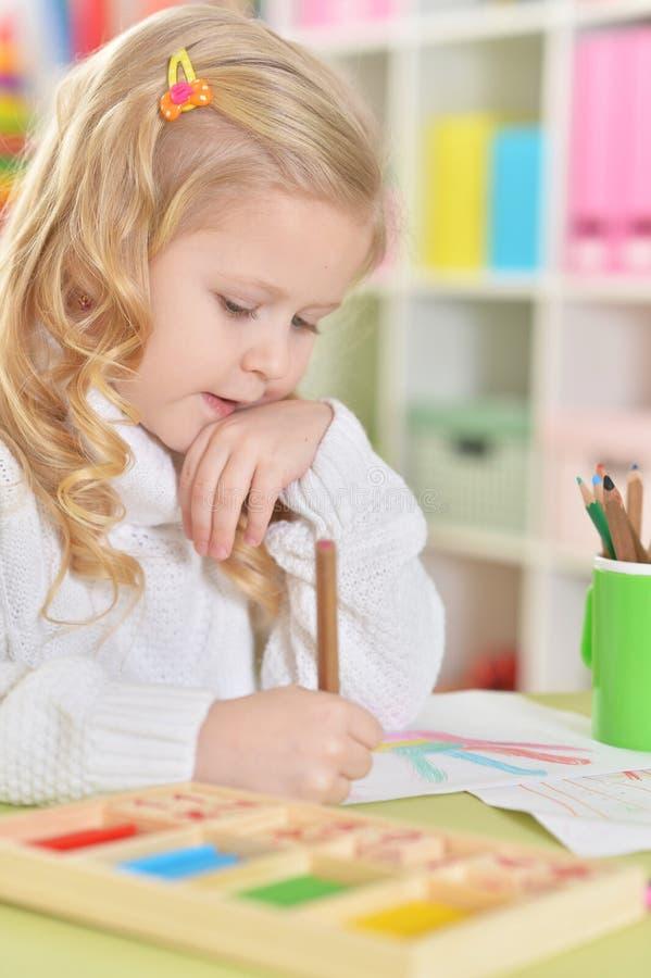 画与五颜六色的铅笔的一个愉快的女孩的画象 库存照片