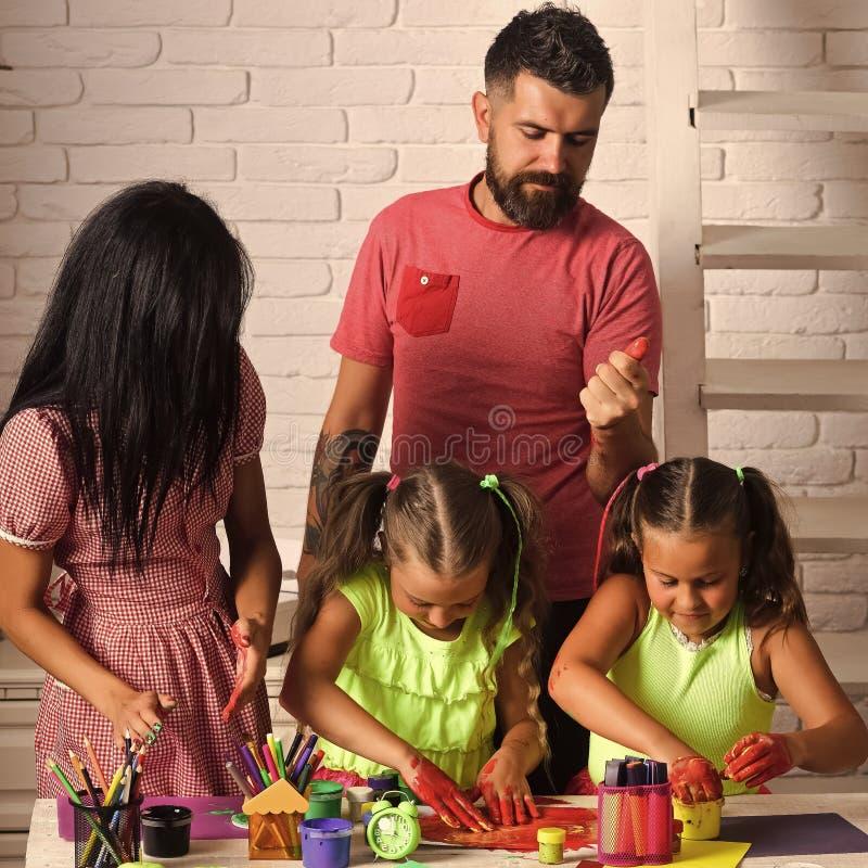 画与母亲和父亲的女孩 童年愉快做父母 想象力,创造性概念 手指画法 免版税库存图片