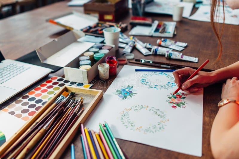 画与蜡笔的女性设计师特写镜头花卉构成坐在工作场所包围与油漆,树胶水彩画颜料 库存照片