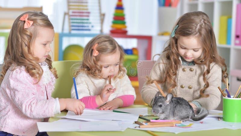 画与铅笔的三逗人喜爱的女孩画象  免版税库存图片