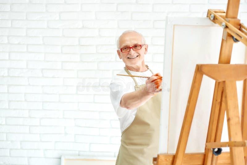 画五颜六色的绘画的英俊的资深画家在明亮的演播室 库存图片